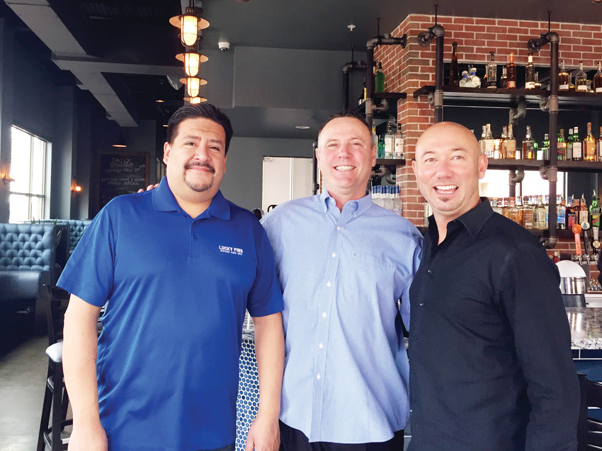 From left, general manager Frank Ortega and manager Dan Greenberg of Smokin' Fins Arvada stand with Smokin' Fins partner Ken Boyle in the newly opened eatery in Olde Town Arvada.