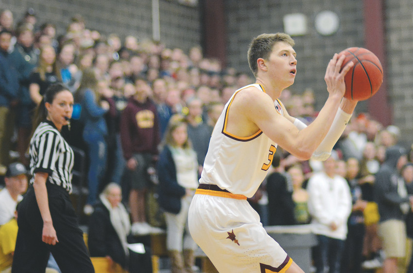 Golden senior Adam Thistlewood set up for a 3-pointer as the Demons' student section looks on Nov. 30. Thistlewood had 23 points in Golden's season-opening 51-44 victory against Holy Family.