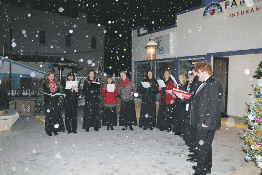 Snow falls softly on members of the Elizabeth High School choir singing carols as part of the Dec. 5 tree auction. The event auctioned 20 decorated trees and the proceeds of each auction was donated to a charity designated by the buyer. The event raised more than $4,000 that was distributed to 14 different charities.