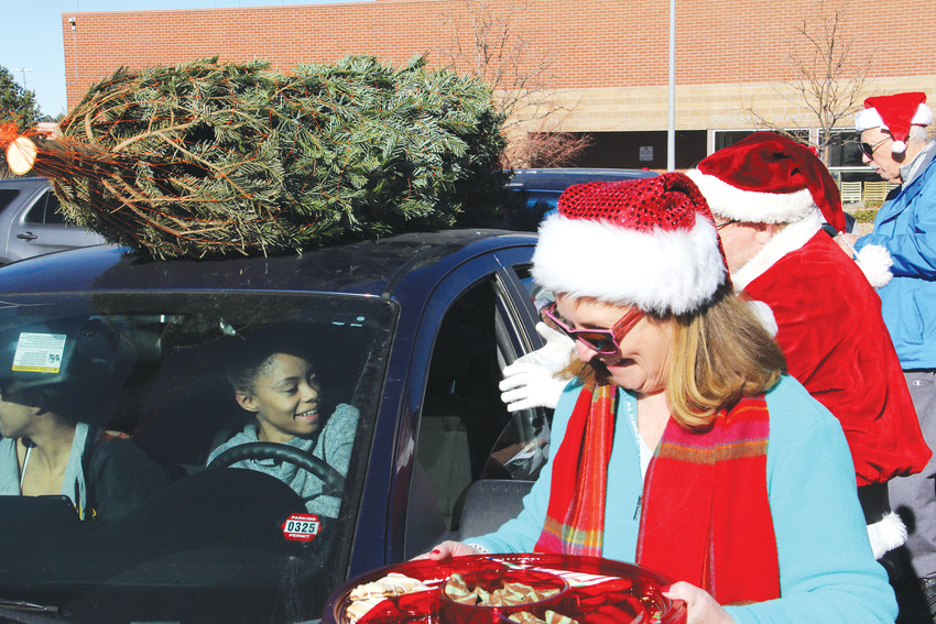 Reejahnae Long, 21, in the driver's seat, smiles as volunteers with the Rotary Club of Centennial help give her a Christmas tree and snacks Dec. 10. Long, who lives in Denver, came to the event at the Arapahoe County Sheriff's Office parking lot after her mother, who used to live in the area, heard about it.