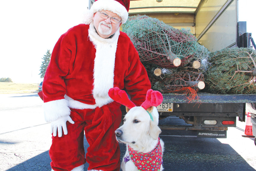"John Peterson, club member, stands with ""Calli the black-nosed reindog"" at a Christmas tree giveaway event Dec. 10. Peterson dressed up as Santa — something he hadn't done since his daughter was a baby 30 years ago —and helped out with the event."