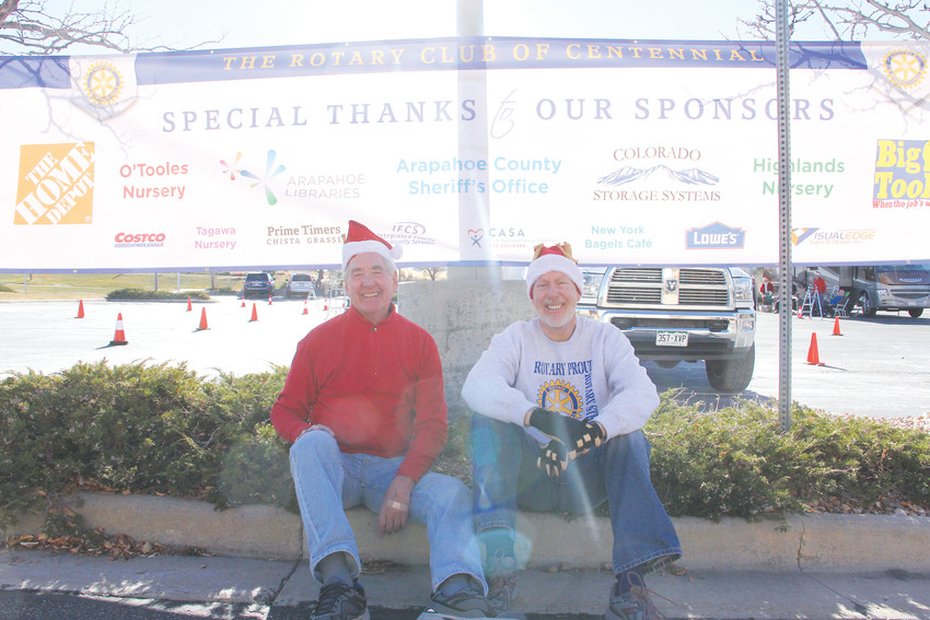Rotary Club of Centennial member Ken Hope, left, and former Centennial Mayor Randy Pye sit at a Christmas-tree giveaway in front of a banner listing sponsors Dec. 10. Current Mayor Cathy Noon also attended the event.
