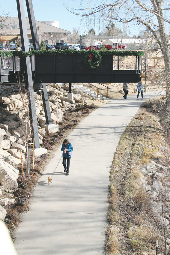 Trails users pass under the lookout at the new Festival Park on Dec. 1.