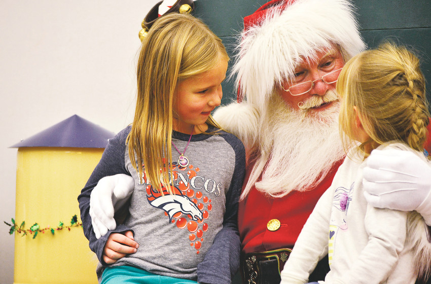 Lily, 6, and Maggie Shackett, 4, of Arvada share their Christmas wish list with Santa Claus at the Jefferson County Library's branch in Olde Town Arvada during the Lagniappe celebration .