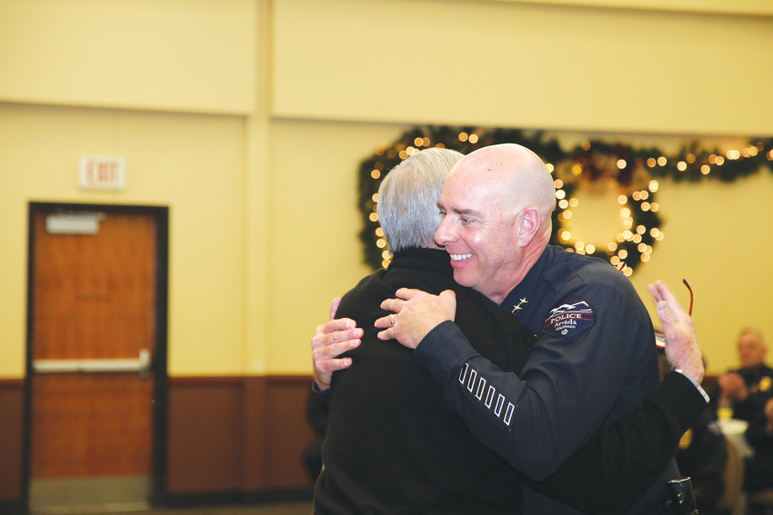 Retiring Arvada Police Chief Don Wick hugs former Arvada City Manager Craig Kocian at a retirement celebration.