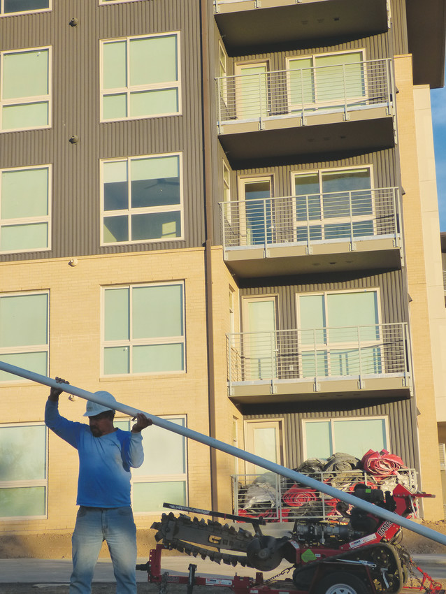 Ciro Soto of Landtech Landscaping lays sprinkler pipe at Vita Littleton, the new apartment complex on Littleton Boulevard, formerly known as the Grove, which will open in May after a lengthy controversy over its size and location.