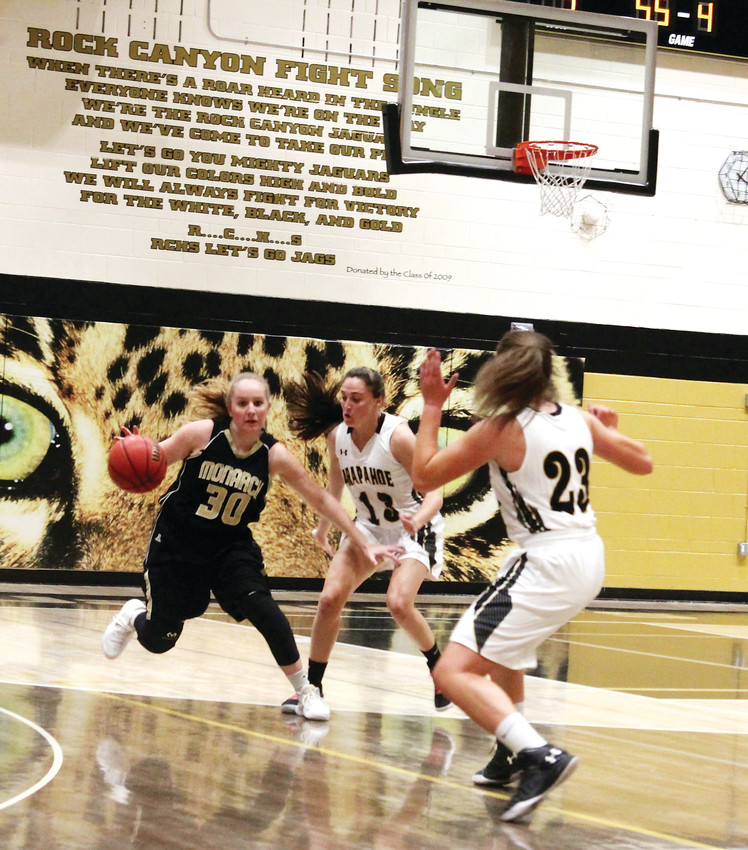 Arapahoe's Grace Cadorette (13) and Anna McCollister (23) apply defensive pressure on a Monarch player bringing the ball up court during the Warriors' 57-26 victory in a season-opening tournament.
