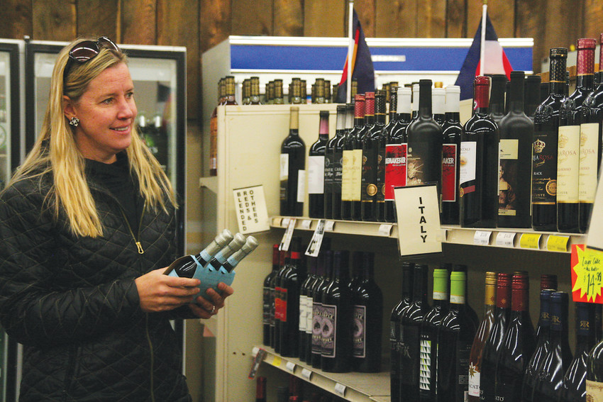 Sarah Pokorny of Golden shops for a holiday gift exchange at Foss Building Wine & Spirits, 1224 Washington Ave. in Golden, on Dec. 14. A friend from Golden Women in Business recommended the store, Pokorny said, because she had heard the store was closing at the end of the year.