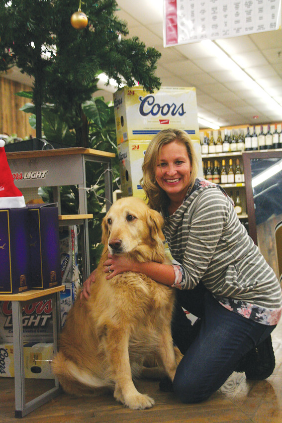 Brittany DeCarlo and Bella have their picture taken inside Foss Building Wine & Spirits, 1224 Washington Ave. in Golden. DeCarlo has owned the liquor store for 10 years. The store's last day for business will be New Year's Eve.