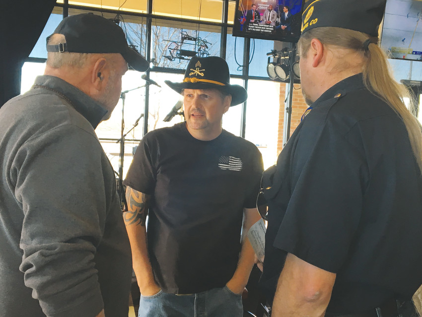 Christian Redman, center, talks with Mike Endres, left, and Cmdr. Doug Osborne, right, of the American Legion Post 1864, which presented Redman with $400 at the Dec. 9 fundraiser.