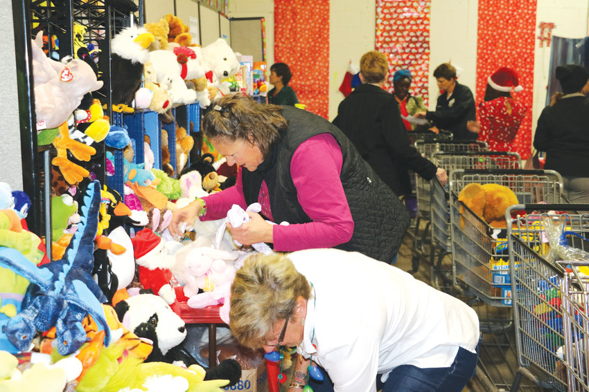 "Action Center volunteers help restock the stuffed animals section of the annual Santa Shop. More than 600 volunteers keep the operation running smoothly for the six days its running. ""High rent prices are causing problems for many families in the area,"" said Barbara Penning, director of volunteer programs and in-kind donations with the center. ""We don't want parents to fall behind on rent or utility payments because they're buying gifts, so we're here to help them."""
