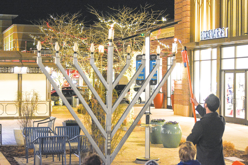 Dr. Zach Amdurer, of Arbor Family Medicine, lights the first Chanukah candle of an outdoor menorah at the Orchard Town Center on Dec. 12. The ceremonies were conducted by Chabad of Northwest Metro Denver.
