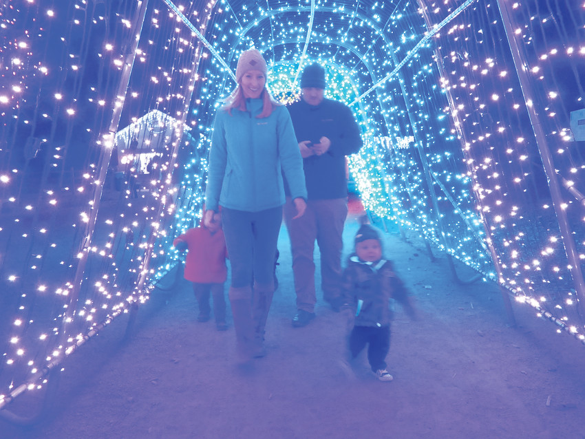 "Dana Gryniewicz, left, and husband Rory and son Mason, 1, stroll through the tunnel of lights. ""Mason's loving this,"" Rory said. ""His eyes are just lighting up."""