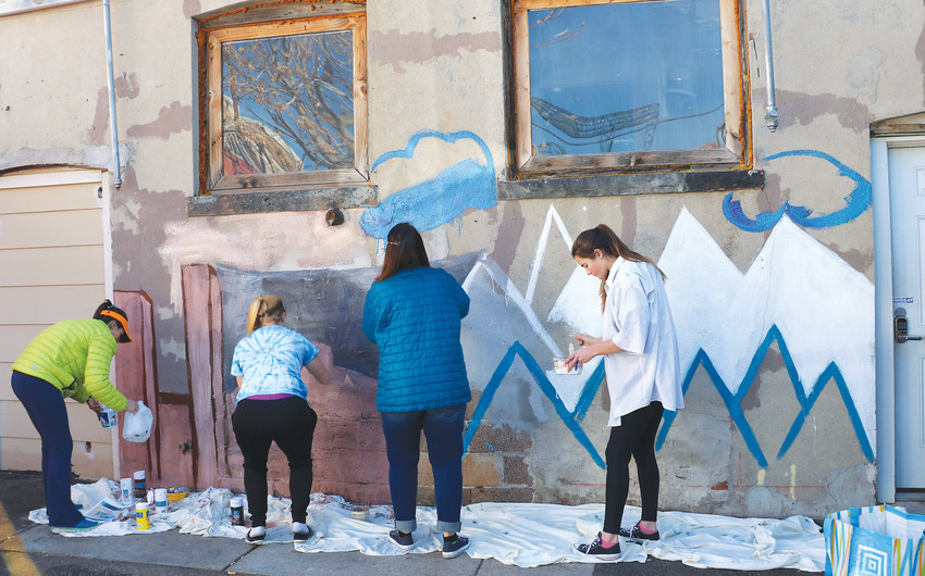 Zoe Tessier, left, Sammy Bumann, Debbie Luhnau and Olivia Luhnau work on a mural in downtown Denver on a December afternoon. Tessier, an art teacher at Rock Canyon High School, planned the project for her students to teach and apply 21st century art styles.