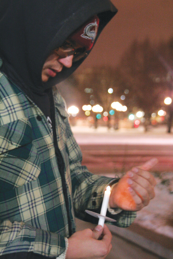 Cody Peterson of Denver cups his hand around his candle to keep the wind from blowing out the flame during the 28th annual We Will Remember: Homeless Persons' Memorial Vigil.