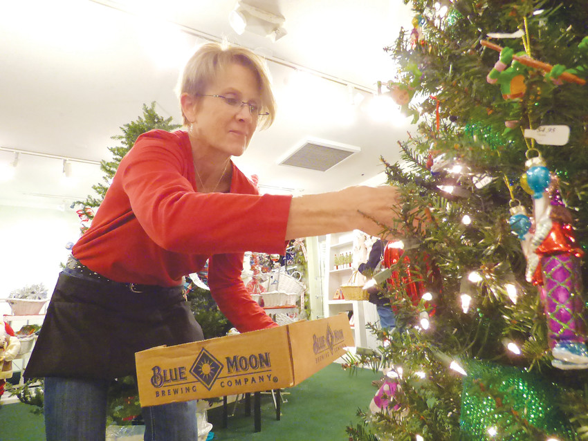 Teri Stouder takes ornaments off a tree on her last day this season at St. Nicks.