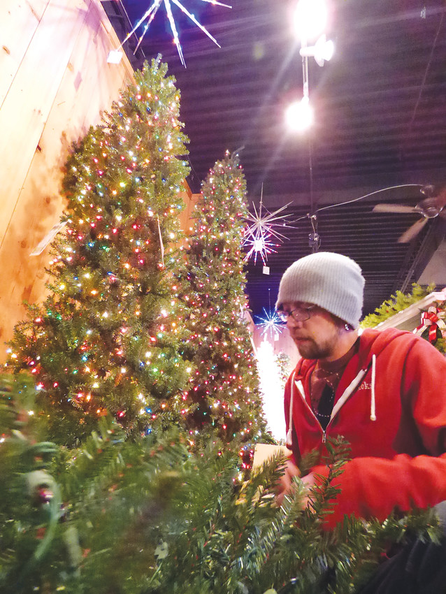 Clint Siderius sets up an artificial tree to replace one sold off the sales floor.
