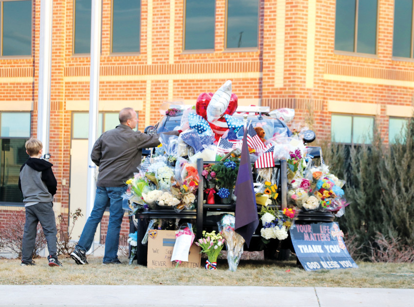 Community members add to a growing memorial at the Highlands Ranch sheriff's office substation Jan. 1 in honor of Douglas County Deputy Zackari Parrish, who was shot and killed on Dec. 31.