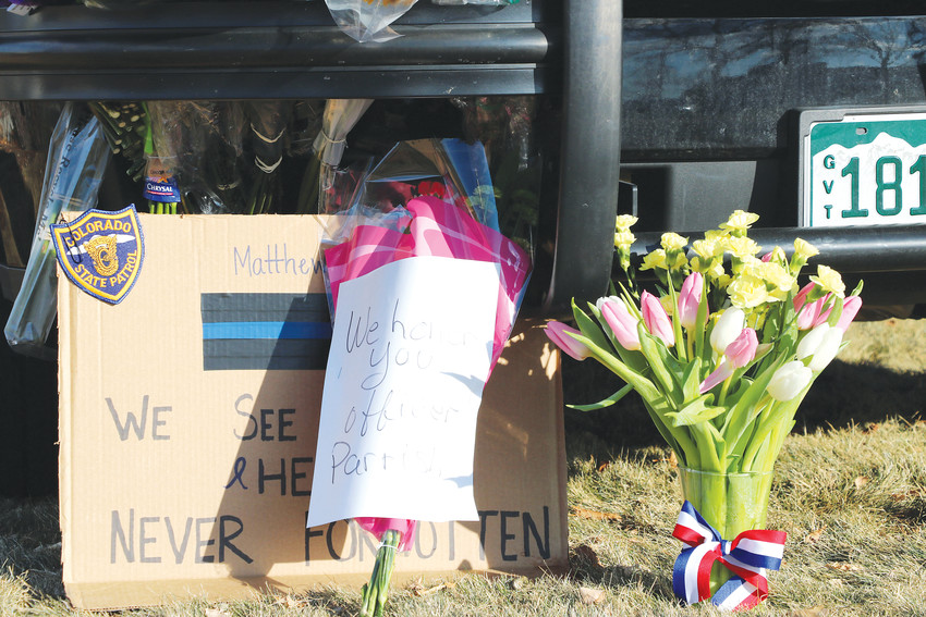 Flowers, balloons and messages cover a Douglas County Sheriff's Office car parked in front of the substation in Highlands Ranch. The memorial honors Zackari Parrish, a deputy killed in the line of duty on Dec. 31.