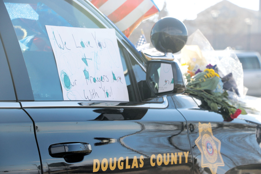 A memorial grows on a Douglas County Sheriff's Office car parked outside of the sheriff's substation in Highlands Ranch, 9250 Zotos Drive, in honor of Zackari Parrish, a deputy killed in the line of duty on New Year's Eve.