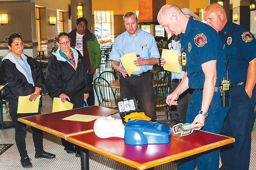 Castle Rock firefighters demonstrate how to use an AED at the Outlets at Castle Rock, where the department recently donated two of the devices.