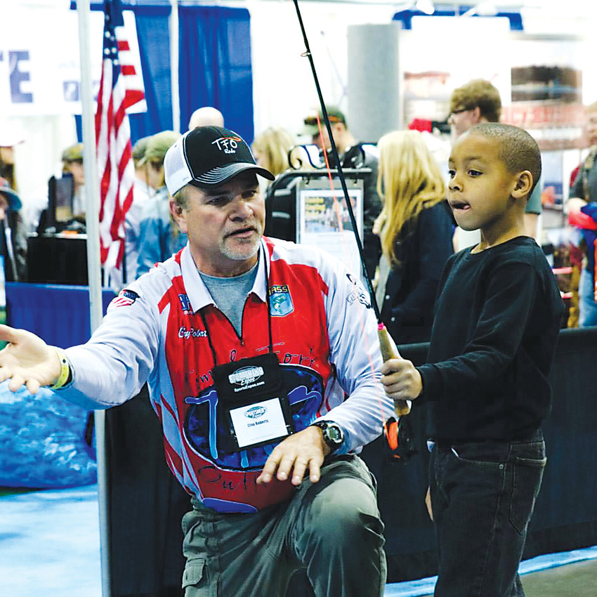 A demonstrator teaches a young man the basics of casting a fly rod. Anglers of all skill levels can learn the craft, and get some tips and tricks, during the Denver International Sportsmen's Expo.