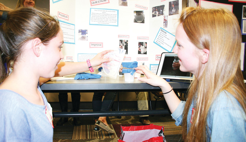 Bell Middle School students Morgan Brodnax, 12, and Sasha Bandock, 13, set up their salt water filtration device at the Girls in STEM competition on Feb. 22 at the Golden Library.  The last few years have seen the district STEM offerings noticeably increase.
