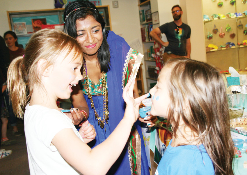 Mitchell Elementary kindergarten students, Lilah Winge, left, and Bryn Call take turns decorating each other's faces as Debalina Mukhopadhyay assists, during Mitchell Elementary School's Multicultural Night.