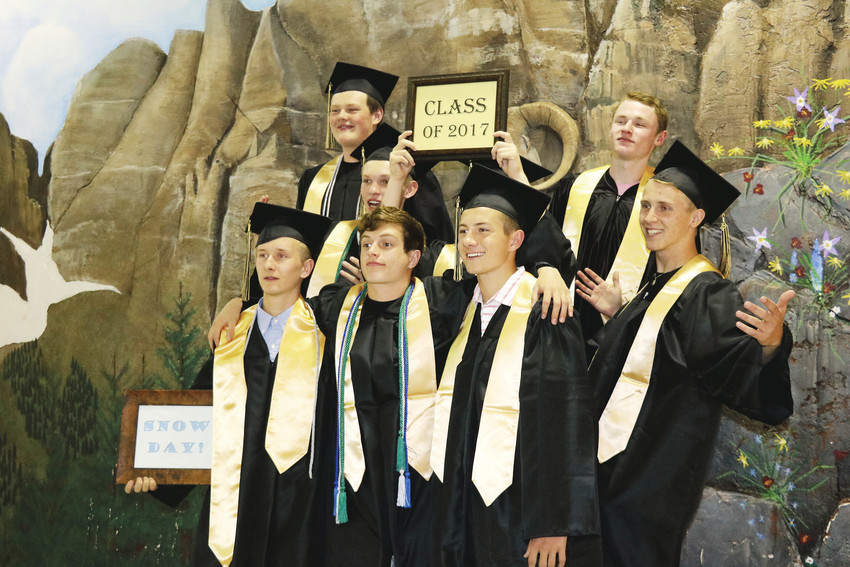 Green Mountain High School's graduation ceremony on May 18 was scheduled for Red Rocks, but snowy weather changed the plans. School staff turned the cafeteria and gym into a celebration place for the students. Graduating seniors pose before a school mural with signs staff made in honor of the occasion.