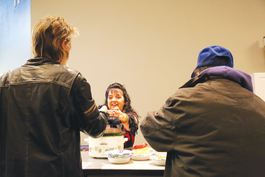 Tina Oltrogge, a volunteer from Storyline Fellowship, serves chili to guests at the severe weather shelter network in Arvada.