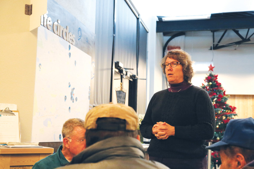 LynnAnn Huizingh, executive director of the Severe Weather Shelter Network, talks to guests and volunteers at the Mile High Vineyard in Arvada during a sheltering night.