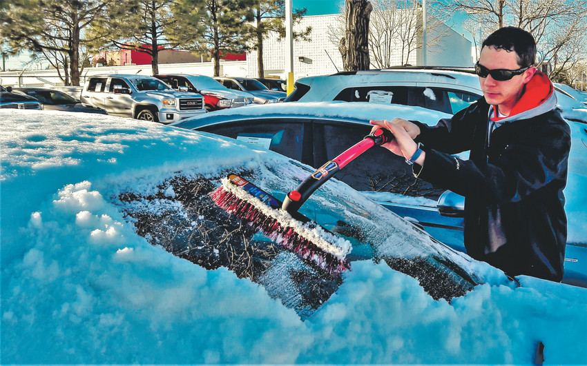 Jason Walling clears snow from the windshield of his car after Colorado's Christmas storm. AAA Colorado recommends drivers do more than just clear the snow before tackling the state's winter roads.