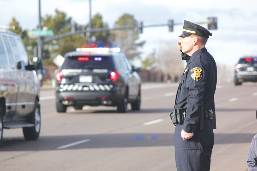 A fellow law enforcement officer stands at attention during the procession for Deputy Zackari Parrish. Photo by Tabatha Stewar