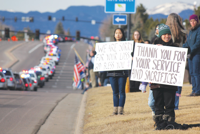 Emma Dreiling, 15, (L) and her sisters came out to honor Deputy Zackari Parrish along Lincoln Avenue. Their mother is a retired Denver police officer. Photo by Tabatha Stewart