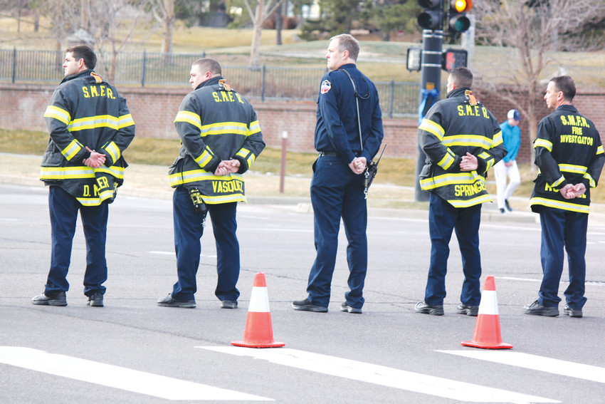 Members of the South Metro Fire Rescue Authority stand watch as the procession for Deputy Zackari Parrish passes on Lincoln Ave. Photo by Tabatha Stewart