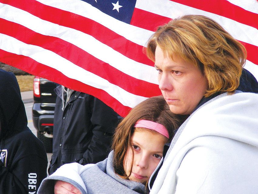 "Roxine Davis, right, holds her daughter Brooklynn as Deputy Zackari Parrish's funeral procession passes. ""When something like this happens far away, it's easier to disconnect,"" Davis said. ""When it's just down the street, the emotion is just so intense."""