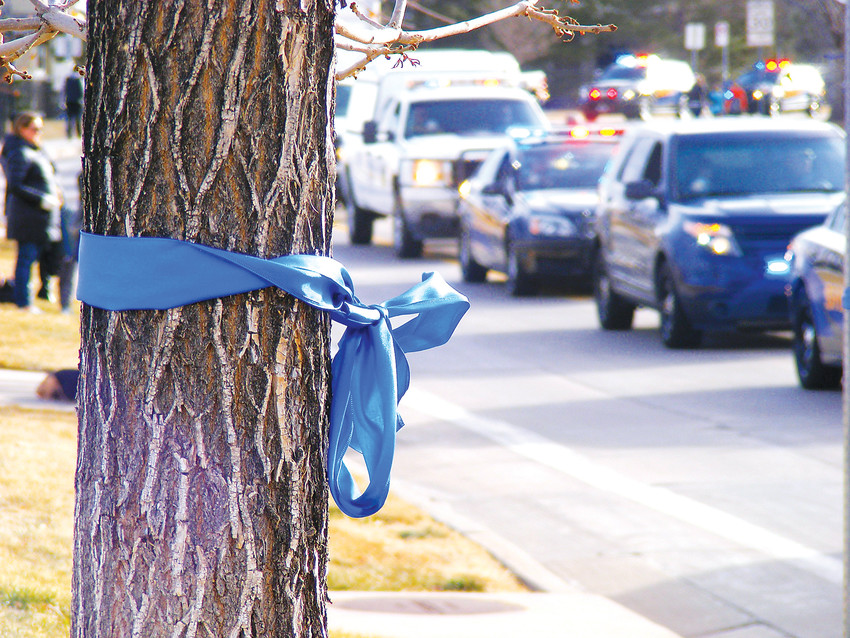 Blue ribbons — symbolizing law enforcement — were hung on trees and fences along the funeral procession route.