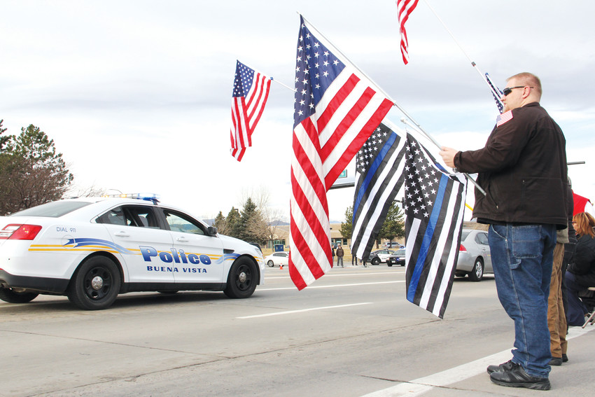 A Buena Vista Police Department car passes civilians lined up along Lincoln Avenue to pay respects in the funeral procession for Douglas County Sheriff's Deputy Zackari Parrish Jan. 5. Crowds lined Lincoln Avenue and South University Boulevard on the way to the funeral.