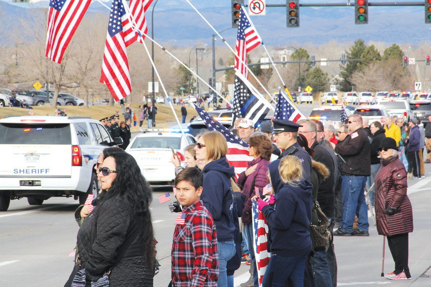 "Civilians lined up along Lincoln Avenue to pay respects in the funeral procession for Douglas County Sheriff's Deputy Zackari Parrish Jan. 5. Families and individuals brought American flags, and some said, ""Thank you for your service"" and ""I'm sorry for your loss"" to passing law-enforcement vehicles."