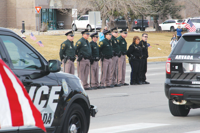 Law enforcement officials stand at Lincoln Avenue and South Quebec Street as Arvada Police Department cars pass in a funeral procession for Douglas County Sheriff's Deputy Zackari Parrish Jan. 5. Parrish, 29, was shot to death in a Highlands Ranch apartment the morning of Dec. 31.