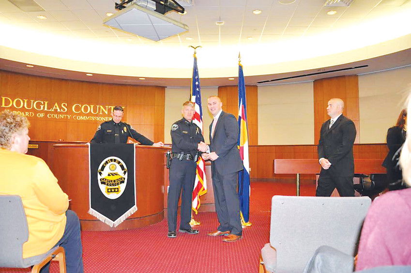Castle Rock Police Chief Jack Cauley, left, and Zackari Parrish shake hands during the January 2015 police department swearing-in ceremony for Parrish.