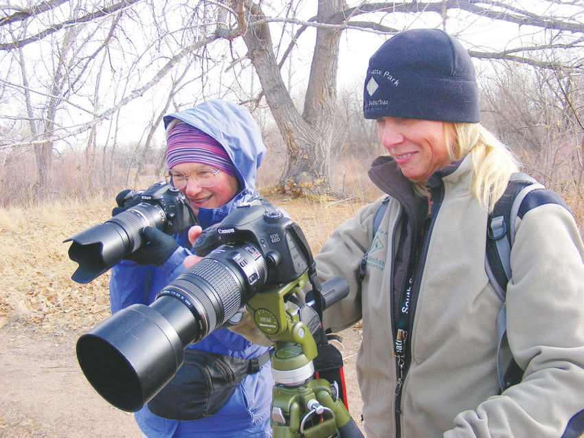 South Platte Park Interpreter Victoria Sutton, left, and Selma Kristel train their lenses on ice in a pond at South Platte Park.