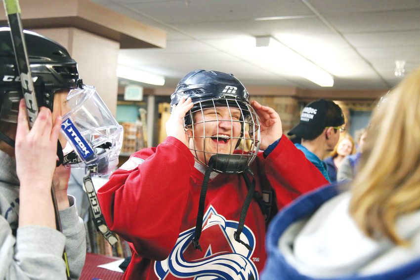 Courtney Tamulis, 28, tries on a helmet before gearing up and hitting the ice with her friends for the DWHL Hockey 101 clinic.