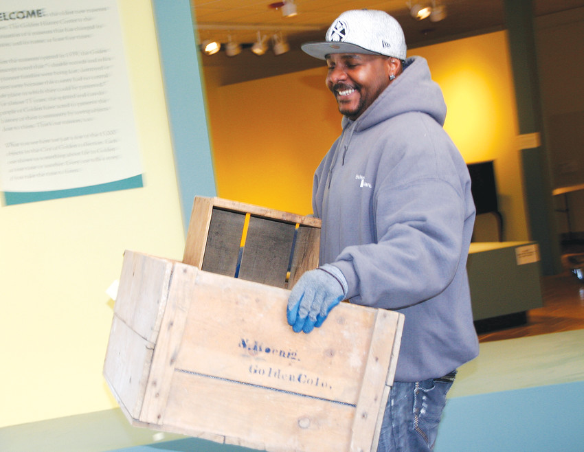 Reginald Holmes with Craters & Freighters, a professional moving company based in Denver, carries a couple of crates to the moving truck on the Golden History Museum's moving day on Jan. 9. The museum's artifacts are being moved to a storage facility in Denver West so the museum can begin its remodel.