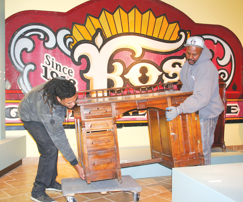 Cody Turner, left, and Reginald Holmes, employees of Craters & Freighters, carefully place a turn-of-the-century desk that once belonged to the Golden Library on a flat with wheels to take it to the moving truck on the Golden History Museum's moving day .