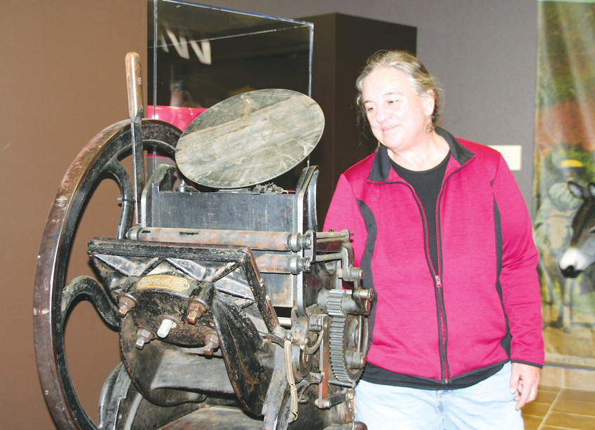 Vanya Scott, a curatorial assistant with the Golden History Museum, looks at a jobbing press dated circa 1890s that was once used by the Colorado Transcript to print smaller items such as stationary, business cards and envelopes.