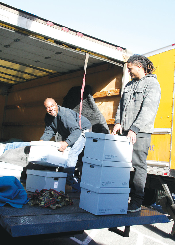 Cortney Cooks, left, and Cody Turner, employees of Craters & Freighters, organize boxes contain some of the Golden History Museum's smaller artifacts in the moving truck on the museum's moving day on Jan. 9.