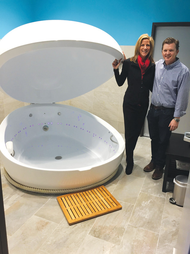Wendy and Erik Skaalerud stand next to a float tank at their new business, Inngi Float, 9567 S. University Blvd., in Highlands Ranch. The float tank differs from others in the industry in its cleaning mechanism and its ability to open and close at a user's discretion.