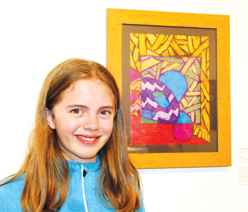 Shelton Elementary School sixth-grader Casey Hume stands next to her original art piece, a depiction of a panda made of marker and crayon, on Jan. 18 at the Foothills Art Center's member preview event for Power of Process: A Jeffco School Exhibition and the art center's Members' Show.