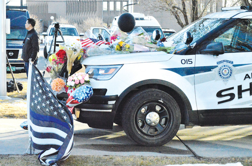 Flowers, candles, stuffed animals and balloons decorate an Adams County Sheriff's Department cruiser outside of the Department substation at 74th and Colorado Boulevard Thursday. Mourners and well wishers began dropping off mementos Thursday morning at the makeshift memorial for slain Deputy Heath Gumm.
